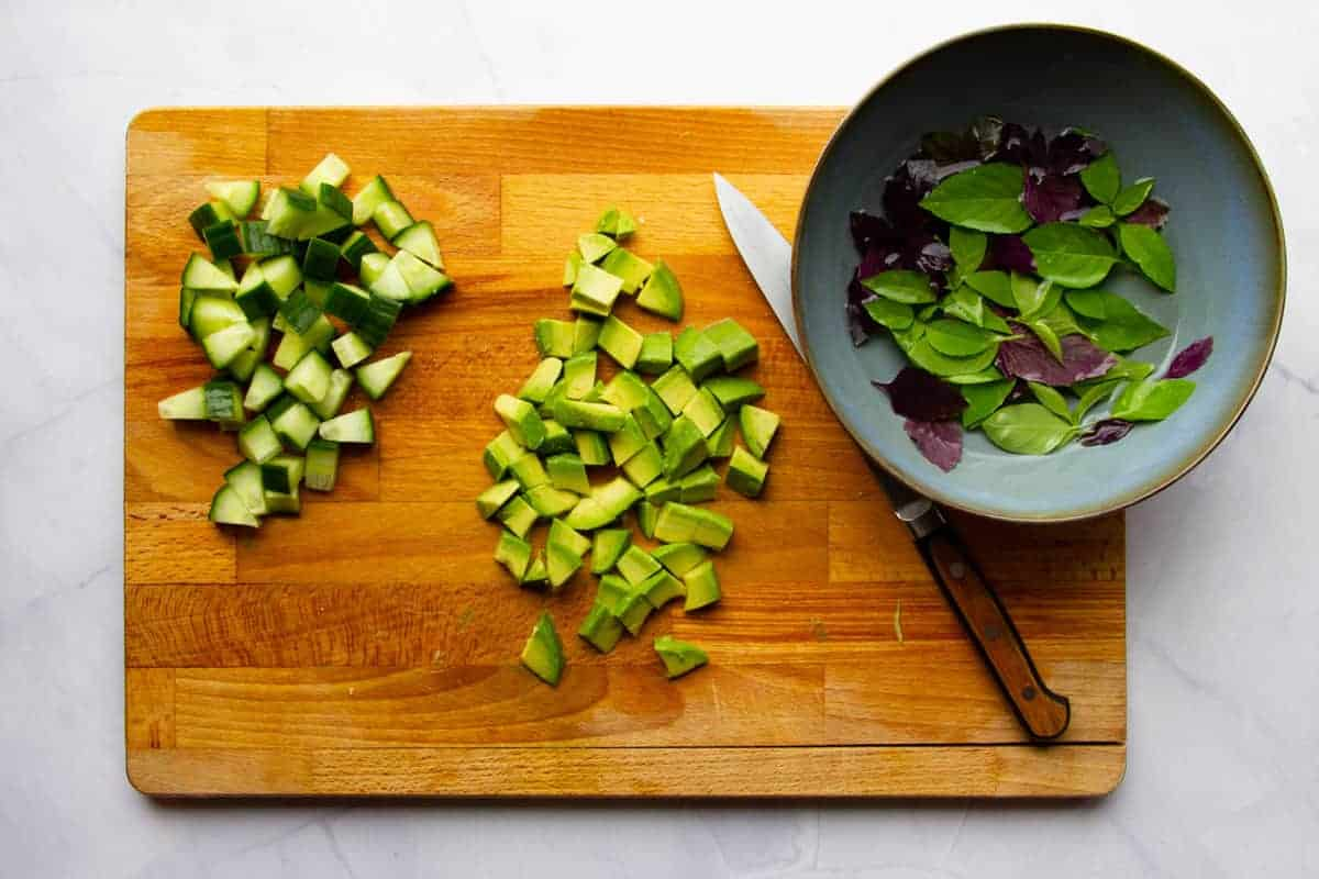 Cutting the cucumber and avocado into bite sized pieces.