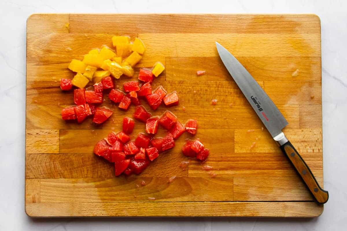 Cutting the grapefruit and orange into cubes.