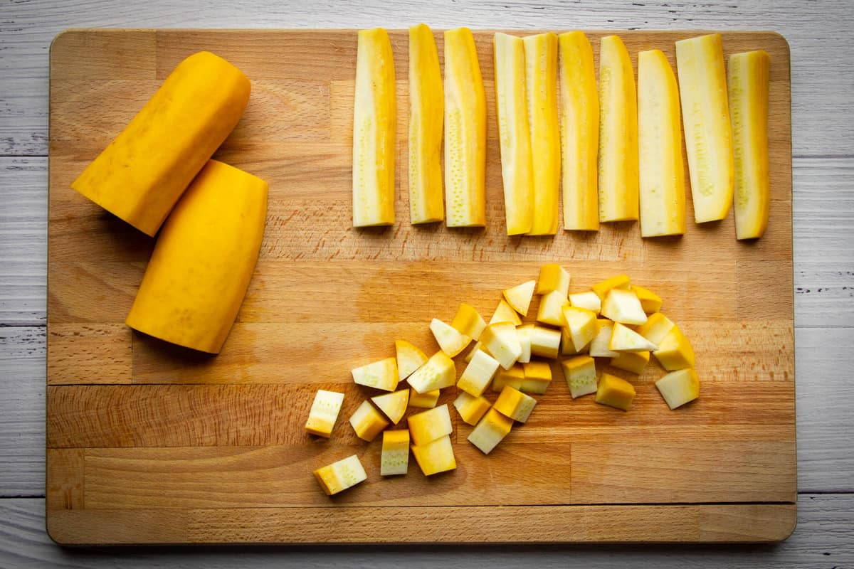 Yellow zucchini cut into cubes on a cutting board.