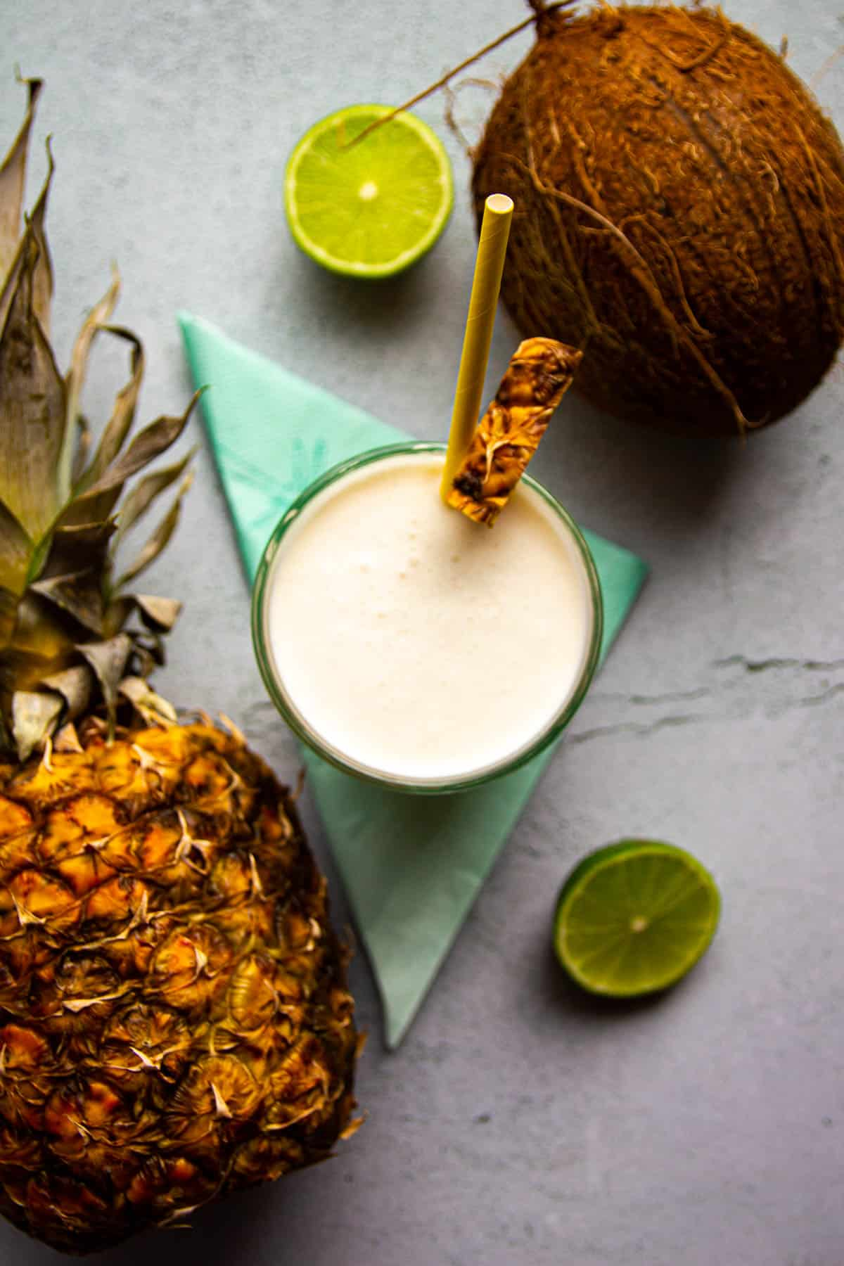 A pina colada on the table with fresh pinapple and coconut in the back.