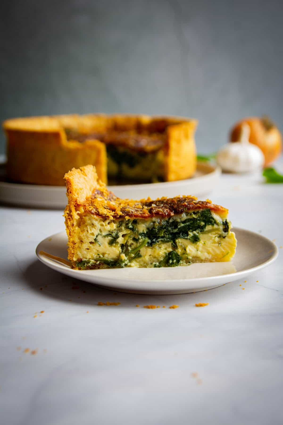 Side angle shot of a slice of quiche florentine with the rest of the quiche in the background.