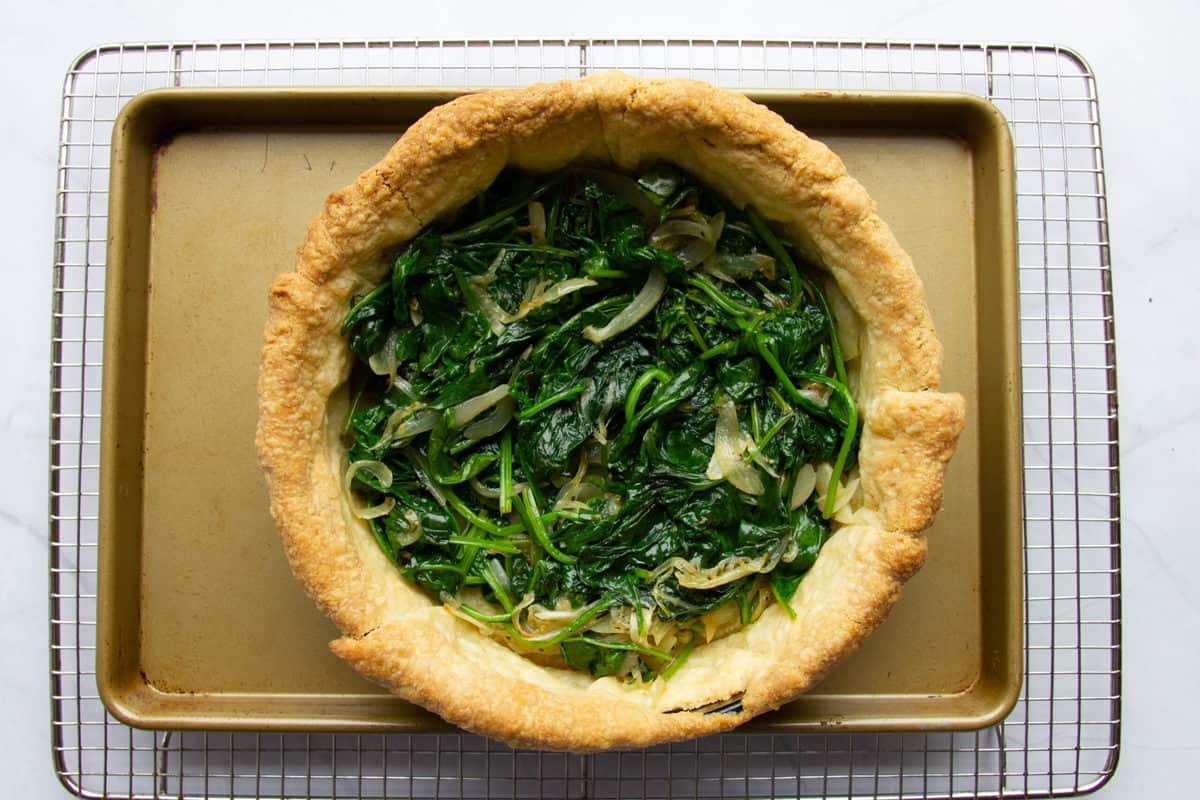 Adding the cooked spinach to the quiche.