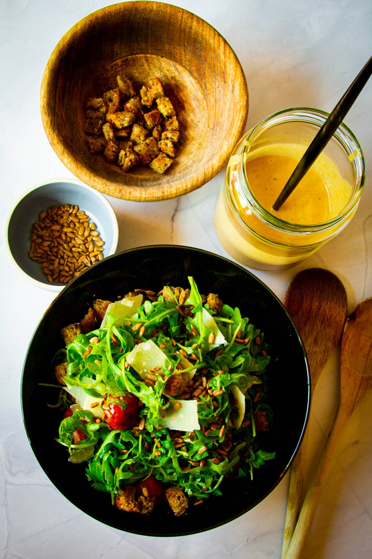 A rocket salad, sunflower dressing, croutons and sunflower seeds on the table.