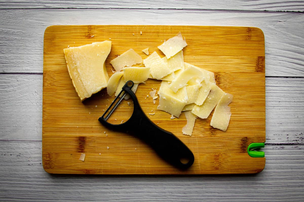 Using a speed peeler to peel the cheese.