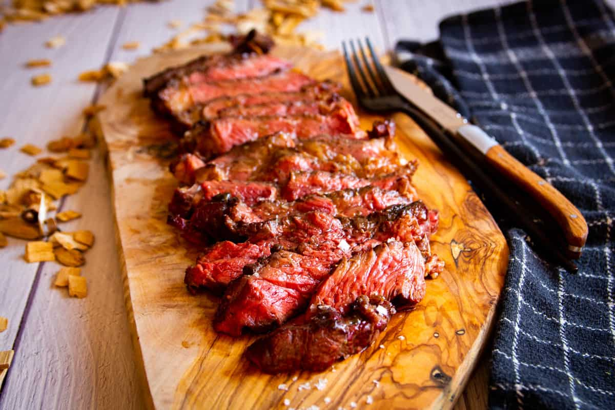 A smoked, reverse-seared ribeye sliced on a wooden board with smoke in the background.