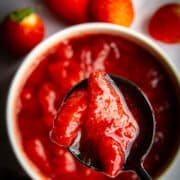 Strawberry sauce in a pot with a spoon.