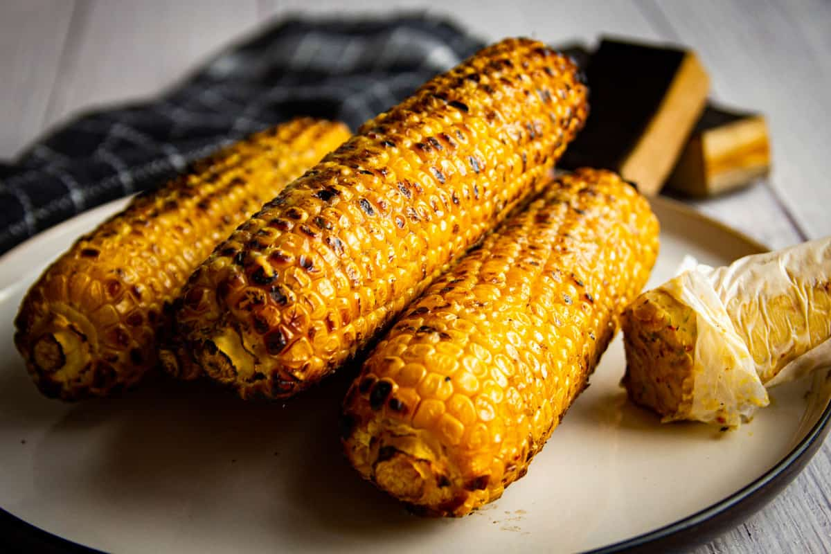 The smoked and grilled corn on a plate with umami butter on the side.