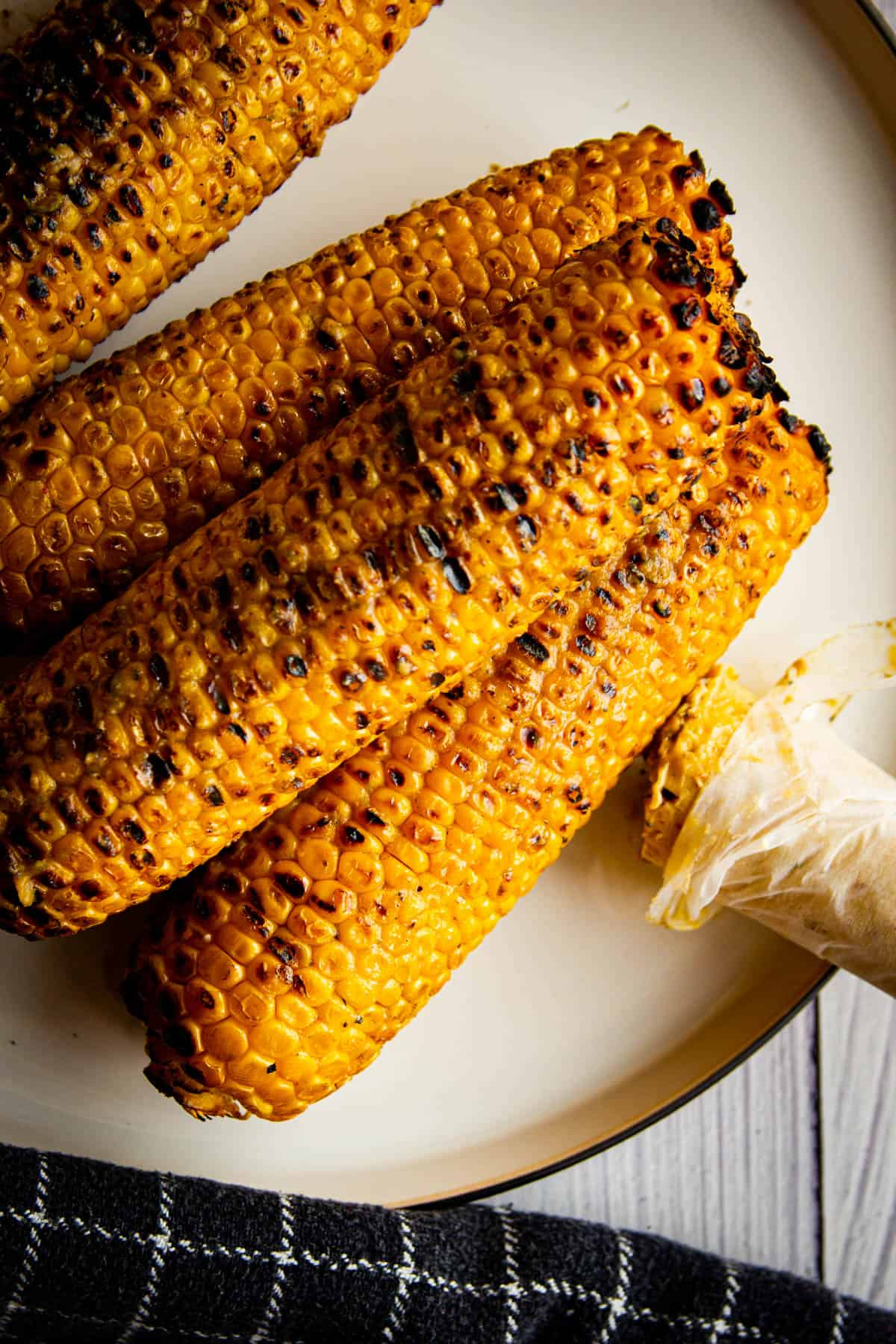 Roasted and charred corn on a plate with umami butter on the side.