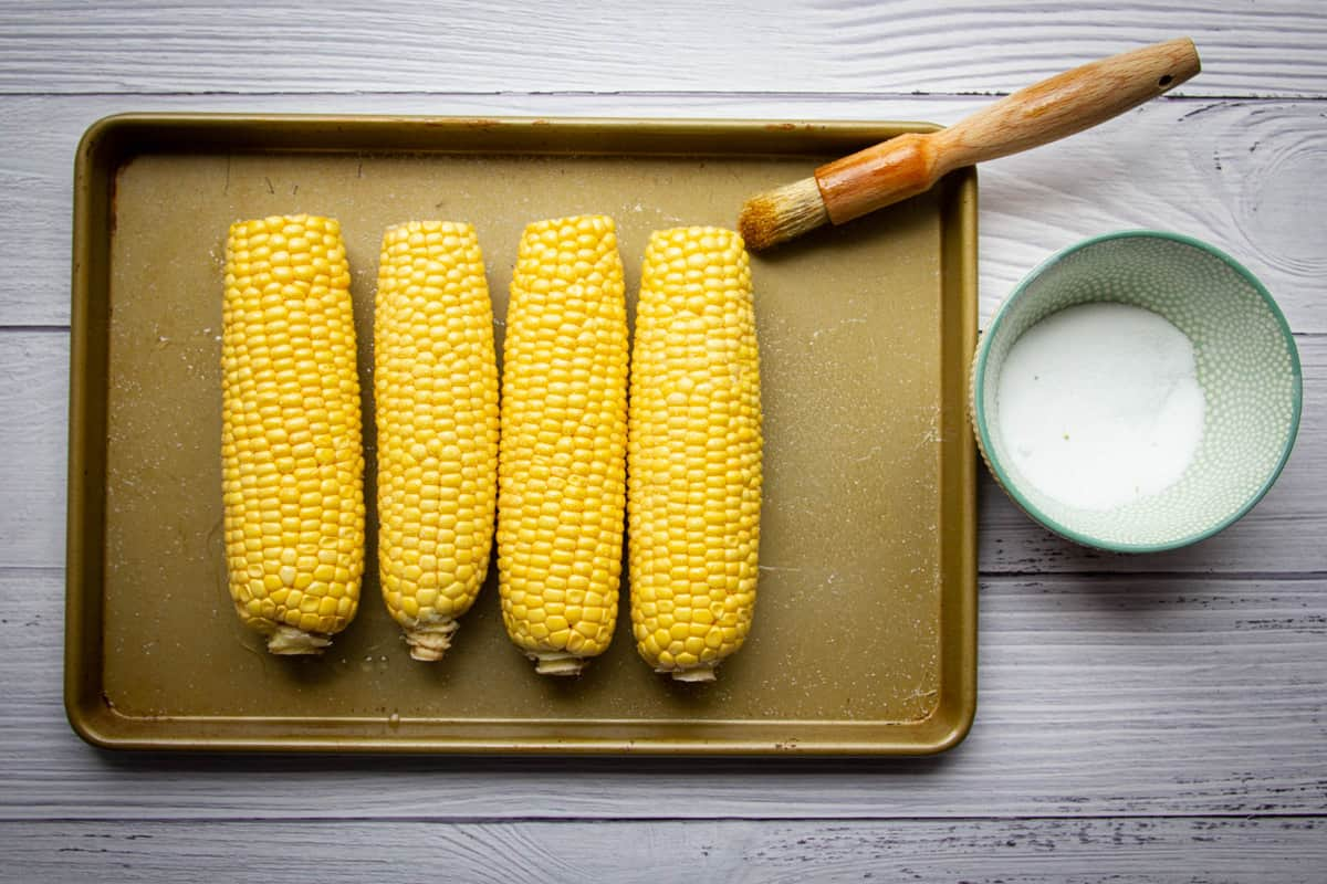 Seasoning the corn cobs with oil and salt.