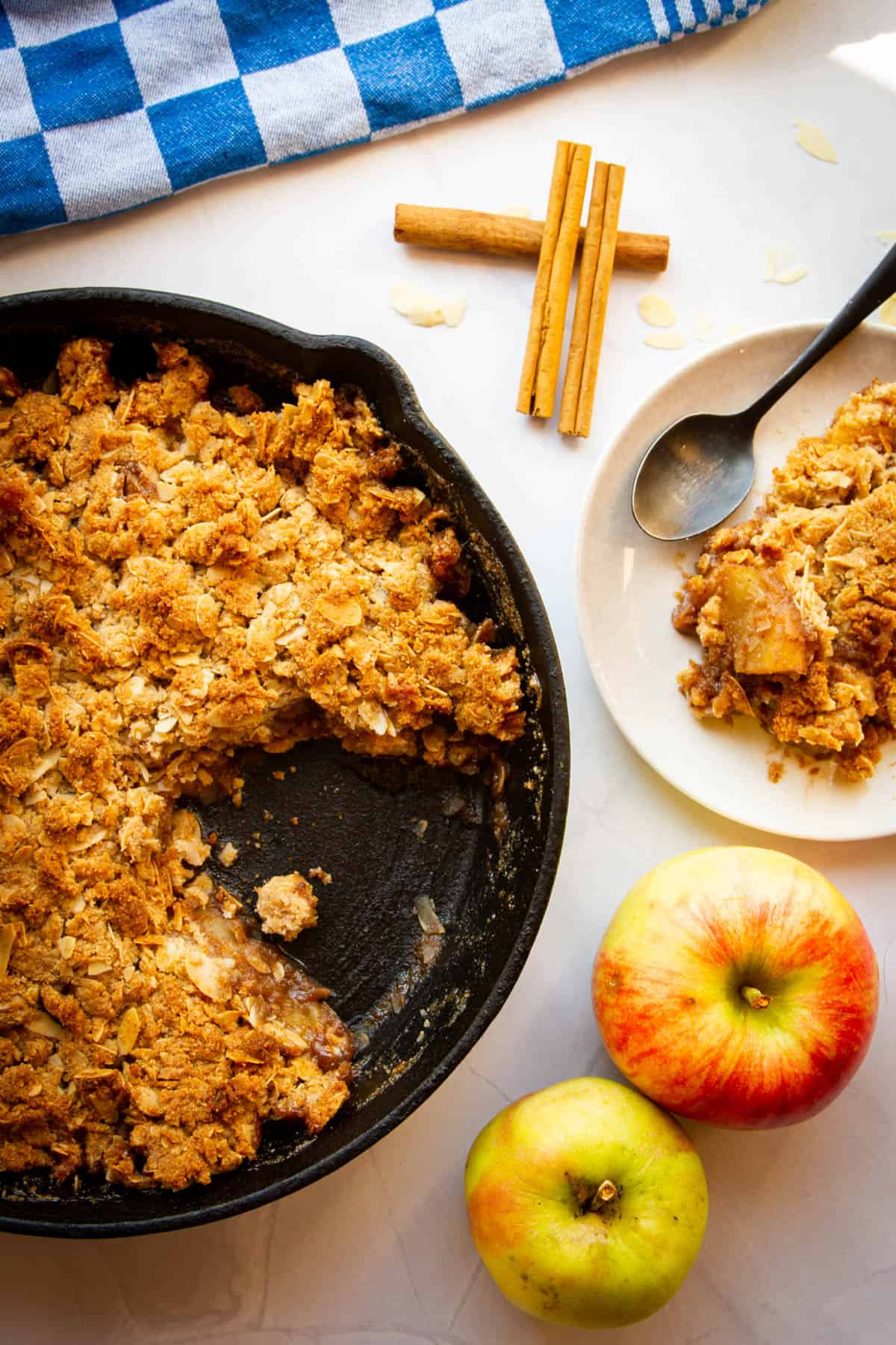A slice of apple crisp on a plate with the rest of the apple crisp behind