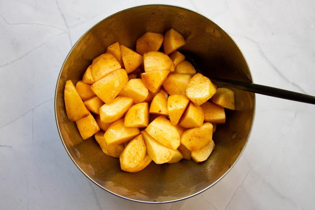 Tossing the apple slices in a bowl with the spices, lemon juice, cognac and icing sugar.