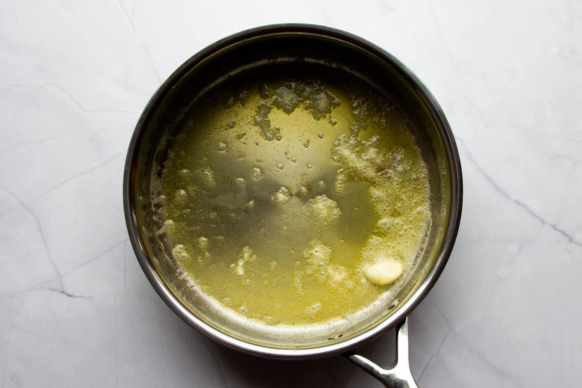 The butter melted in a pan with one clove of garlic.