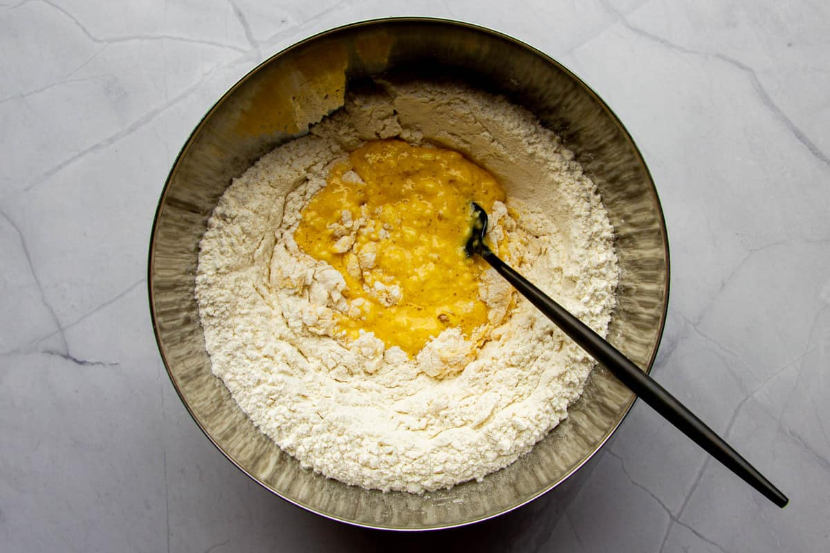 Mixing the eggs slowly into the flour.