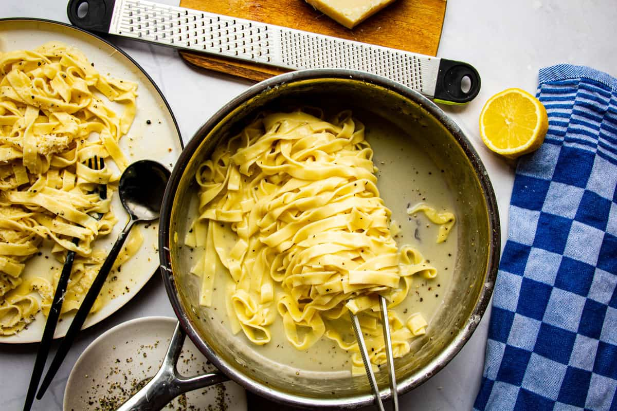 Tagliatelle cacio e pepe in a pan with a plate on the side.