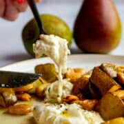 A fork scoopin into a piece of burrata on a plate with roasted pears, thyme, marcona almonds and brown butter.