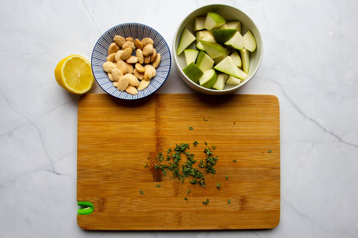Pears, almonds, thyme and a lemon ready to go in separate bowls.
