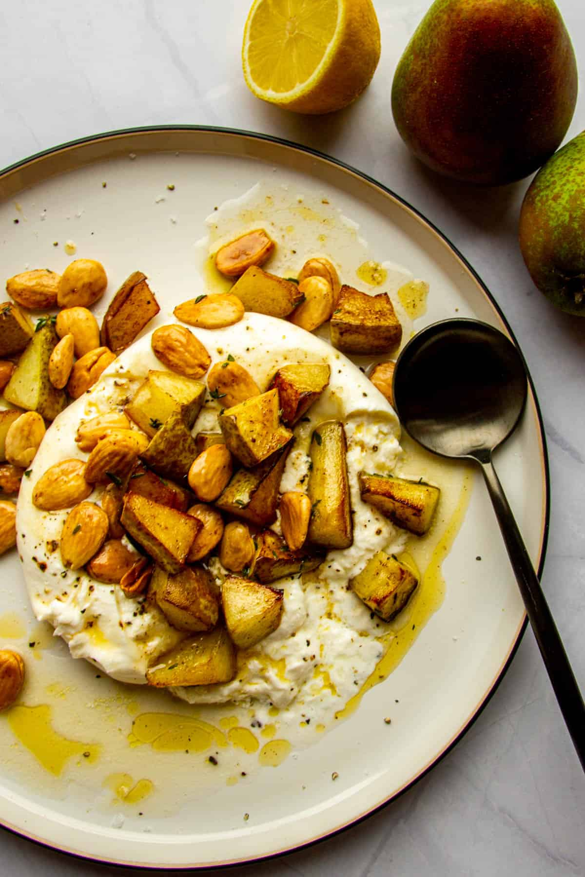 Whole burrata on a plate with roasted pears, thyme, marcona almonds and brown butter