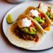 Instant pot carnitas in soft tacos with guacamole, tomato salsa and creme fraiche on top.